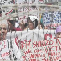 Looking for recognition: Filipino women who say they were forced into sexual slavery during the war hold a rally behind barbed wire outside the Malacanang presidential palace in Manila on Saturday. | AP