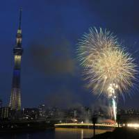 Brief bang: Fireworks light up the sky Saturday along the Sumida River in Tokyo before it was canceled by a thunderstorm. | KYODO