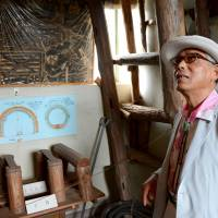 Cold trail: South Korean Choi Rak-hun, whose father is believed to have worked at the Kajima coal mine in Fukuoka Prefecture during World War II, looks at exhibits of the mine in June in Miyawaka, Fukuoka Prefecture. | KYODO