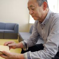 Survivor's tale: At home recently in Hiroshima, Tokihiko Hara holds his uncle's notebook detailing his experiences of the atomic bombing of the city. | KYODO