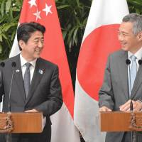 Sharing the stage: Prime Minister Shinzo Abe (left) and his Singaporean counterpart, Lee Hsien Loong, smile during a joint door-stop interview at the Istana presidential palace in Singapore on Friday. | AFP-JIJI