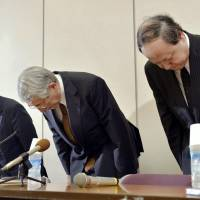 Bitter pill: Toshikazu Yoshikawa (center), president of Kyoto Prefectural University of Medicine, and other university executives apologize before reporters Thursday night in Kyoto.   | KYODO