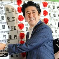 Red-letter day: Prime Minister Shinzo Abe places rosettes beside the names of Liberal Democratic Party candidates who won seats in Sunday's House of Councilors election. | SATOKO KAWASAKI