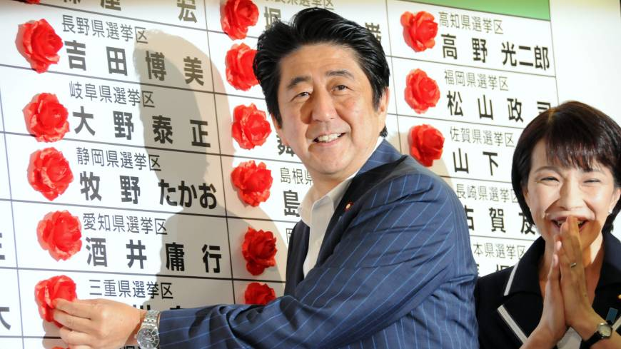 Red-letter day: Prime Minister Shinzo Abe places rosettes beside the names of Liberal Democratic Party candidates who won seats in Sunday's House of Councilors election.