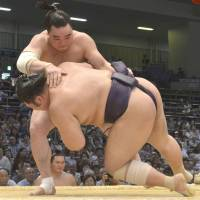All in a day's work: Yokozuna Harumafuji defeats No. 2 maegashira Tochiozan on Friday at the Nagoya Grand Sumo Tournament.  | KYODO