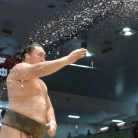 Already done: Hakuho throws salt prior to his match against Kotooshu at the Nagoya Grand Sumo tournament on Friday. Hakuho clinched the title with two days to spare.   | KYODO