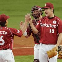 Chalk up another win: Eagles pitcher Masahiro Tanaka (18) is congratulated by teammates Kazuya Fujita and Motohiro Shima after Tuesday's game ended at Kyocera Dome. Tanaka won his 17th consecutive decision dating back to last season in Tohoku Rakuten's 4-1 triumph over Orix. | KYODO