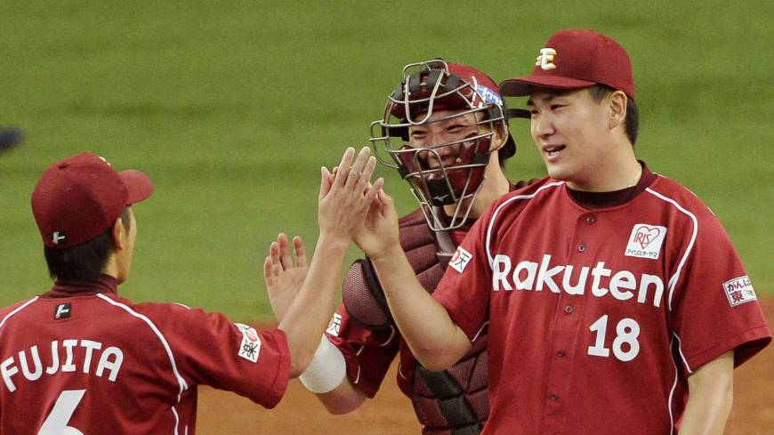 Chalk up another win: Eagles pitcher Masahiro Tanaka (18) is congratulated by teammates Kazuya Fujita and Motohiro Shima after Tuesday's game ended at Kyocera Dome. Tanaka won his 17th consecutive decision dating back to last season in Tohoku Rakuten's 4-1 triumph over Orix.