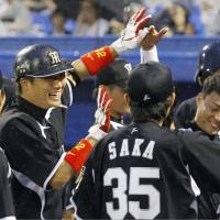 The hits keep coming: Hanshin's Ryota Arai, left, celebrates with his teammates after his two-run homer against Yakult on Wednesday. The Tigers won 12-0. | KYODO