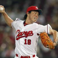 On target: Hiroshima's Kenta Maeda pitches against Yokohama on Wednesday. The Carp routed the BayStars 11-3. | KYODO