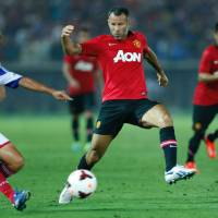 Seen it all before: Manchester United's Ryan Giggs (center) defends against Yokohama F. Marinos' Yuta Narawa during their exhibition match at Nissan Stadium on Tuesday. | AP