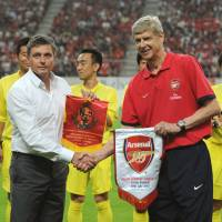 The legend returns: Arsenal manager Arsene Wenger (right) shakes hands with Nagoya Grampus counterpart Dragan Stojkovic in a pre-match ceremony at Monday night's friendly at Toyota Stadium in Aichi Prefecture. | AFP-JIJI