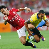 No walk in the park: Arsenal's Theo Walcott (right) and Urawa's Yuki Abe vie for the ball during Friday's friendly in Saitama. | AP