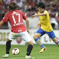Single objective: Arsenal's Ryo Miyaichi attempts to move the ball past Urawa's Mitsuru Nagata on Friday. | KYODO