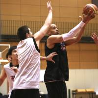 All for country: J.R. Sakuragi (right) takes a layup as Sean Hinkley goes for a block during Japan's national team training camp at the National Training Center on Sunday. | KAZ NAGATSUKA