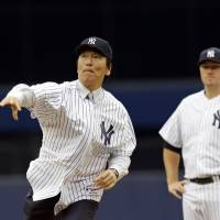 High heat: Hideki Matsui throws out the ceremonial first pitch as Yankees starter Phil Hughes watches prior to New York's 6-5 win over Tampa Bay on Sunday. | AP
