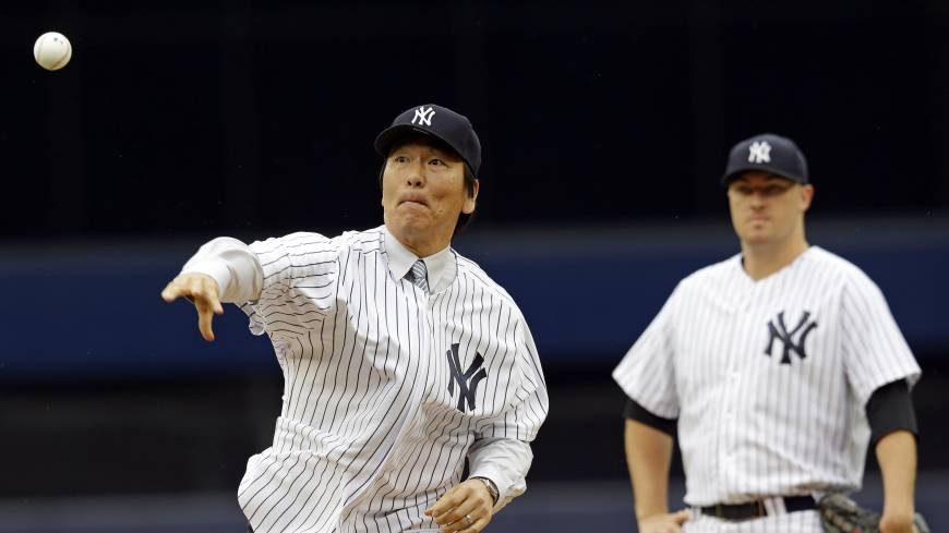 High heat: Hideki Matsui throws out the ceremonial first pitch as Yankees starter Phil Hughes watches prior to New York's 6-5 win over Tampa Bay on Sunday.