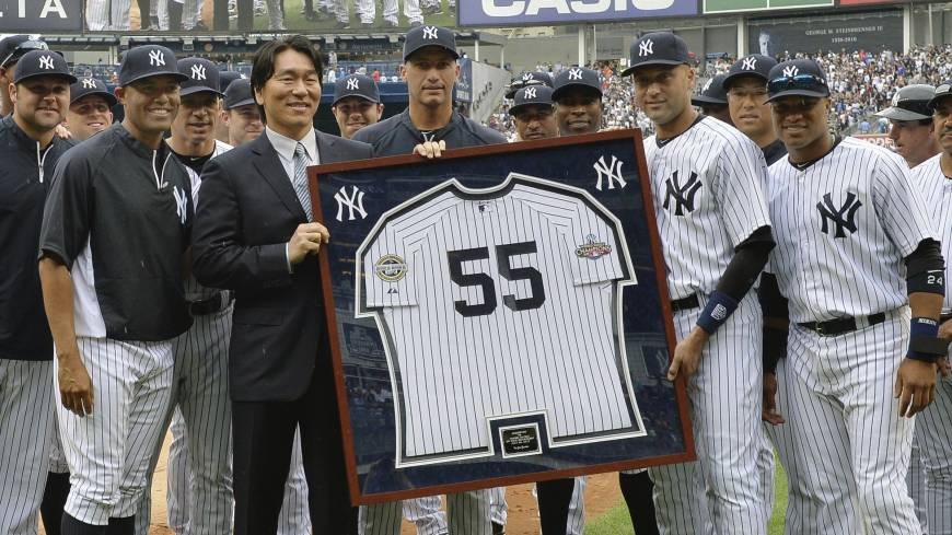 True Yankee: Hideki Matsui, left, and Yankees captain Derek Jeter hold a framed Matsui jersey while surrounded by members of the Yankees on Sunday in New York.