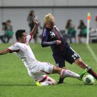 First impressions: Yojiro Takahagi (right) was one of several players making their debuts for Japan at the East Asian Cup in South Korea last week. | AP