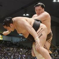 He's behind you: Hakuho (right) pushes Aminishiki out of the ring at the Nagoya Grand Sumo Tournament on Sunday. | KYODO