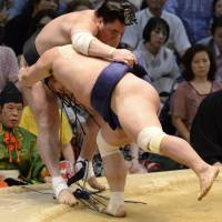 Head first: Myogiryu (right) shoves Harumafuji out of the ring at the Nagoya Grand Sumo Tournament on Monday. | KYODO