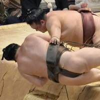 Down he goes: Yokozuna Hakuho tumbles out of the raised ring on Saturday at the Nagoya Grand Sumo Tournament, giving Kisenosato a victory over his yokozuna rival. | KYODO