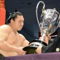 A winner's reward: Yokozuna Hakuho is handed the Emperor's Cup for the 26th time in his illustrious career on Sunday. Hakuho took home the top prize at the Nagoya Grand Sumo Tournament. | KYODO