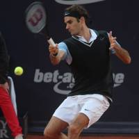 Pushed hard: Roger Federer plays a shot from Germany's Florian Mayer in their quarterfinal match at the German Tennis Championships on Friday. Federer won 7-6 (7-4), 3-6, 7-5. | AP