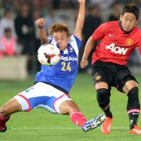 Tight defense: Manchester United's Shinji Kagawa (right) shoots the ball while Yokohama F. Marinos defender Yuta Narawa attempts to block it during Tuesday's friendly at Nissan Stadium in Yokohama. Marinos won 3-2. | AFP-JIJI