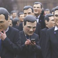 On the same page: Dozens of protesters wearing masks depicting British finance chief George Osborne hold a rally against tax avoidance in London in March. | REUTERS/KYODO