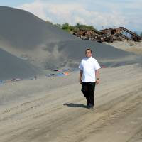 Beyond salvation: Catholic priest Sammy Rosimo follows truck tread marks past piles of fine black sand at an abandoned magnetite mine along the coast in the town of Caoayan, which lies in Ilocos Sur province north of Manila. | AFP-JIJI