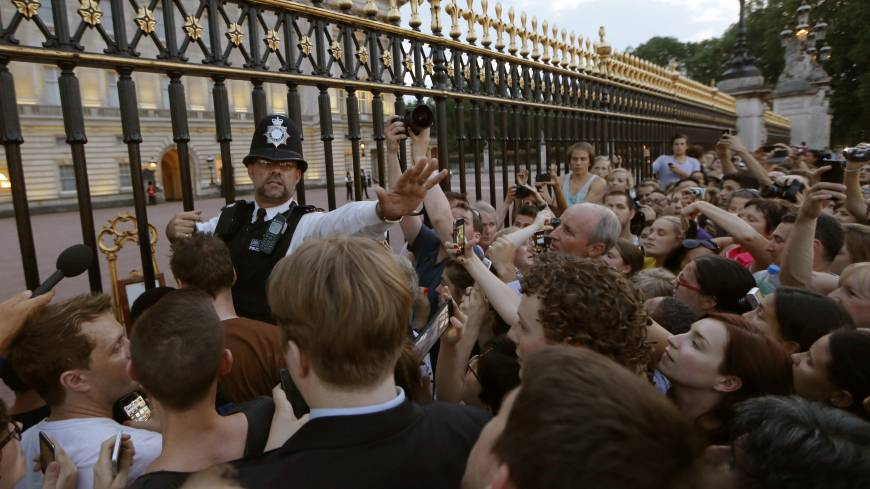 Siege at the gates: A police officer tries to control a crowd attempting to get to the fence of Buckingham Palace in London to take pictures of a public notice proclaiming the birth of a baby boy to Prince William and Catherine, Duchess of Cambridge, on Monday.