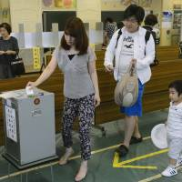 Family duty: A couple, accompanied by their son, cast their votes for the Upper House election at a polling station in Minato Ward, Tokyo, on Sunday morning.  | KYODO