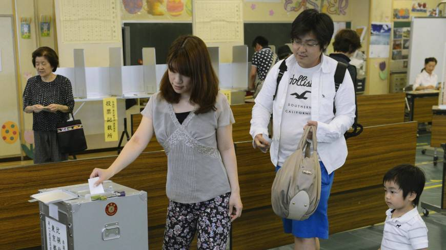 Family duty: A couple, accompanied by their son, cast their votes for the Upper House election at a polling station in Minato Ward, Tokyo, on Sunday morning.