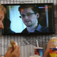 Phantom: Passengers eat in Moscow's Sheremetyevo airport June 26 as Russian TV news reports on Edward Snowden. | AP