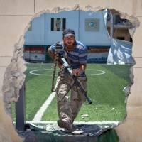 No game: A Syrian rebel passes through a hole in the perimeter wall of a soccer field in Aleppo on Thursday. | AFP-JIJI
