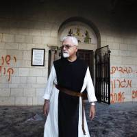 Sinister trap?: A Trappist monk passes graffiti in Hebrew reading 'Jesus is a monkey' and 'mutual guarantee, Ramat Migron and Maoz Ester' (West Bank settlements) at the monastery of Latrun, between Jerusalem and Tel Aviv, in September. | AFP-JIJI