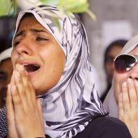 Crying out: Women grieve during a funeral service for opponents of ousted Egyptian President Mohammed Morsi on Saturday in Cairo. The opponents were killed during clashes last week. | AP