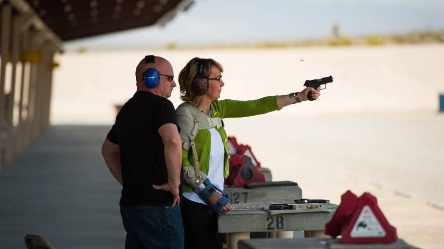 Responsible solutions: Former Rep. Gabrielle Giffords fires a gun for the first time since being shot in Arizona more than two years ago as her husband, Mark Kelly, watches at Clark County Shooting Complex at the kickoff of their Americans for Responsible Solutions tour in Las Vegas on July 1. The couple was traveling to seven states to promote safe gun legislation and chat with locals.