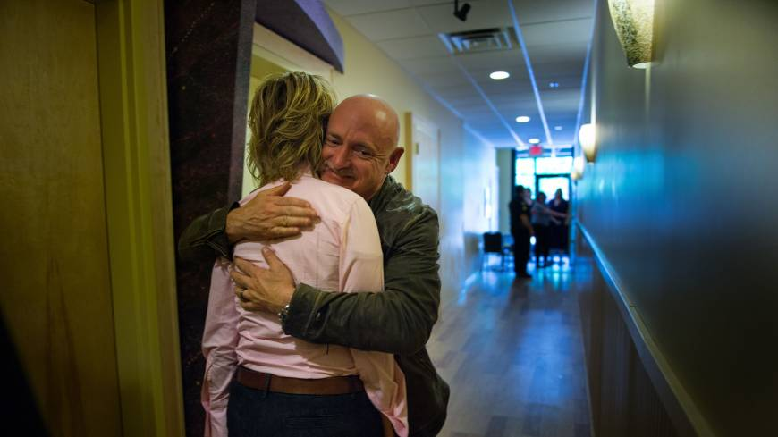 Embracing change: Retired astronaut Capt. Mark Kelly hugs his wife, former Rep. Gabrielle Giffords, before an appearance at Atomic Coffee during the Americans for Responsible Solutions tour in Fargo, North Dakota, on July 3.