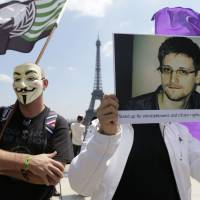 Wanted man: A demonstrator holds up a picture of former National Security Agency contractor Edward Snowden during a protest in support of him in Paris on Sunday. | AFP-JIJI
