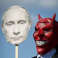 Speak of the devil: An activist wears a devil mask while holding a cutout of President Vladimir Putin as part of a protest against the Russian leader in Hanover, Germany, in April. | AFP-JIJI
