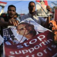 Letting off steam: Opponents of Mohammed Morsi, the ousted Islamist president of Egypt, burn pictures of U.S. President Barack Obama during a rally outside the presidential palace in Cairo on Sunday. | AP