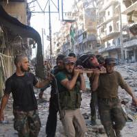 Opposition fighters carry a dead comrade in the Salaheddine neighborhood of Aleppo on Monday. | AFP-JIJI