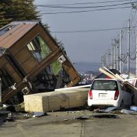 Distant ties: A man walks past a collapsed house and other debris at the port of Sendai on March 12, 2011, following the Great East Japan Earthquake the previous day. New research shows powerful earthquakes overseas can trigger tremors around wastewater injection sites in the U.S. | AP