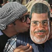 Friends everywhere: A supporter of ousted Egyptian President Mohammed Morsi kisses an acquaintance wearing a Morsi mask during a rally before Friday prayers in Cairo. | AP