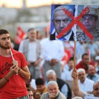 Spillover: Turkish demonstrators supporting ousted Egyptian President Mohammed Morsi hold a banner with the crossed out images of Israeli Prime Minister Benjamin Netanyahu (left) and Egyptian Army chief Abdel Fattah al-Sisi during a pro-Morsi demonstration Sunday in Istanbul. | AFP-JIJI