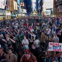Peaceful protest: Throngs of demonstrators gather during a march in New York's Times Square early Sunday for a protest against the acquittal of George Zimmerman in the 2012 killing of 17-year-old Trayvon Martin in Florida. | AP