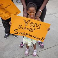 Youth message: Jediah Jones, 3, holds a sign Sunday in Atlanta as her mother, Keiota Jones, stands behind her during a protest the day after George Zimmerman was found not guilty in the 2012 shooting death of teenager Trayvon Martin. | AP
