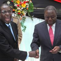 In control: Zimbabwean President Robert Mugabe shakes hands with Prime Minister Morgan  Tsvangirai after he signed the nation's new constitution into law in Harare on May 22. | AP